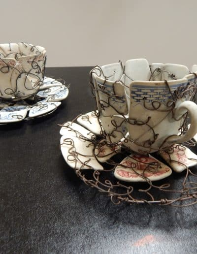 Broken mismatched teacups and saucers reconstructed with wire.