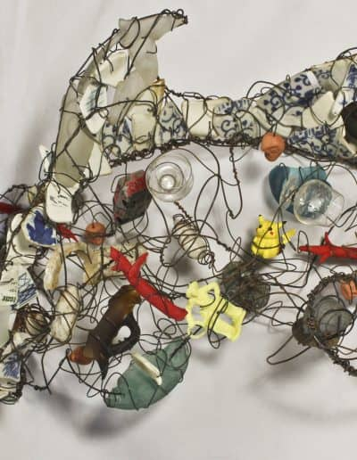 Wave shaped sculpture made with steel wire, tumbled glass shards, beads, rocks, and objects