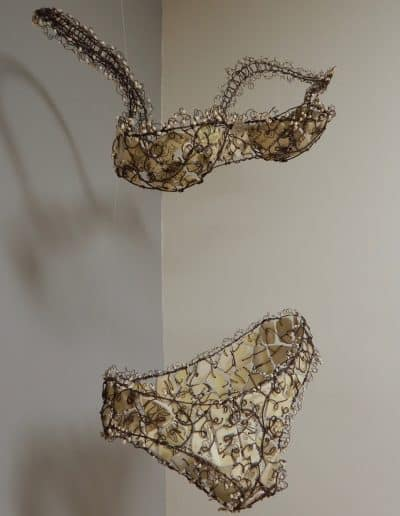 Suspended Bra and Panties sculpture made with wire, broken and tumbled dishes, with wire and glass bead lace around the edges