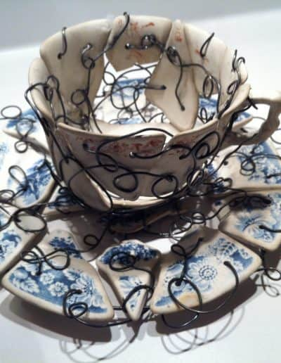 Broken teacup and saucer reconstructed with wire.