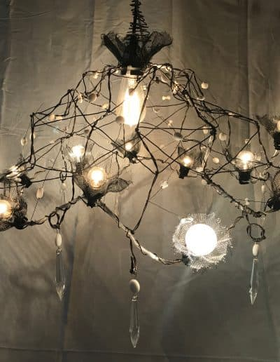 Functional wire chandelier with white beads and aluminum screen ruffles around small bulbs