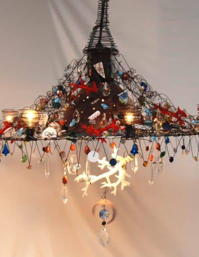 Large chandelier made from salvaged outdoor light with wire and mixed media.